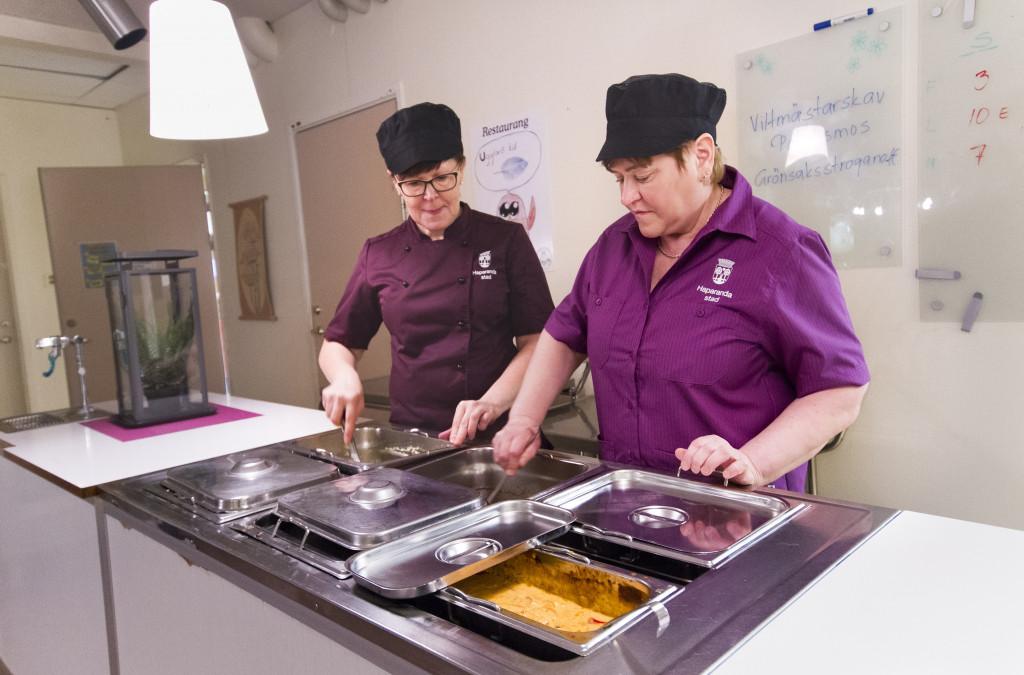 Keittäjä Pirjo Hautajärvi ja keittäjä-siivoaja Eila Kanto tekevät Grankullensskolanin ruuan koulun omassa keittiössä.